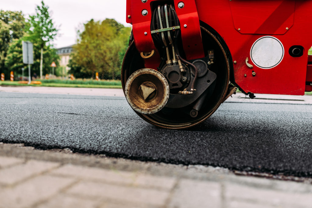 Red road roller paving a new and fresh road.