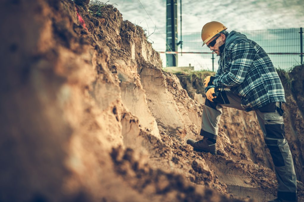 A construction worker analyzes the digging of soil before he continues with his big project